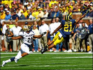 Michigan senior Jeremy Gallon (21) reaches for a pass on Akron senior Malachi Freeman (20) and narrowly misses.