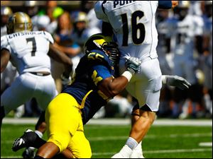 Michigan senior Jibreel Black (55) tackles Akron sophomore quarterback Kyle Pohl (16), forcing him to throw the ball.