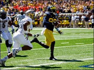Michigan senior quarterback Devin Gardner (98) runs the ball into the end zone for a touchdown.
