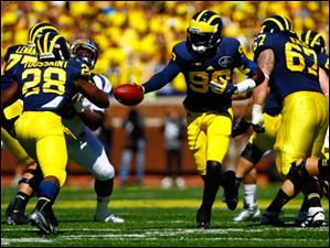 Michigan senior quarterback Devin Gardner (98) hands off the ball to senior Fitzgerald Toussaint during.