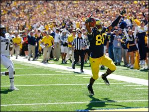 Michigan sophomore Jehu Chesson (36) celebrates as he scores a touchdown on Akron senior Anthony Holmes (7).