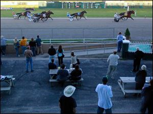 The crowd watches a race during the final weekend for live harness racing at Raceway Park on September 14, 2103.