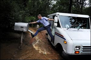 Dave Jackson closes a mailbox with his foot after delivering the mail Friday to a home surrounded on three sides by a flooded Cheyenne Creek.