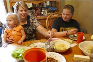 Jodie Banaszak helps her daughter Mackenzie, 2, left, eat while talking with her daughter Cassidy, 10, right, over dinner in their home in Toledo. Jodie has lost 50 pounds since undergoing surgery for a gastric sleeve, which reduced the size of her stomach by 90 percent, two months ago.