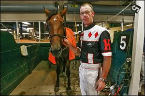 Mark Headworth, standing beside Monstro Hanover, has won more than 2,000 times at Raceway Park.