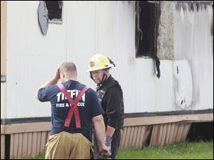 Wm. Timothy Spradlin, Chief of the Fire & Explosion Investigation Bureau with the Division of the State Fire Marshal, right, speaks with a member of Tiffin Fire & Rescue, left, during the investigation into the scene.