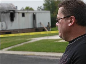 Neighbor Rick Hummell watches as authorities investigate the scene.