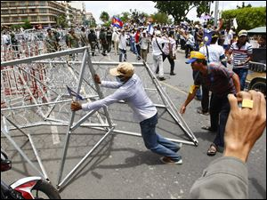 A supporter of Cambodia's opposition parties move barbed wire set up by the police during a gathering on a street for