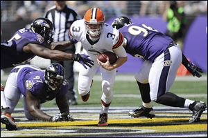 Cleveland Browns quarterback Brandon Weeden scrambles between Baltimore Ravens outside linebacker Terrell Suggs, top left, defensive end Arthur Jones, and defensive end Marcus Spears, right, during the first half today in Baltimore. Weeden left late in the fourth quarter after a possession that produced the Browns' eighth punt.