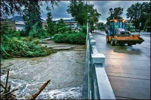 A bulldozer crosses the swollen Boulder Creek  in Boulder, Colo. Water levels have receded as intense rain abated the past two days.  In Boulder County Sunday, 234 people were unaccounted for.