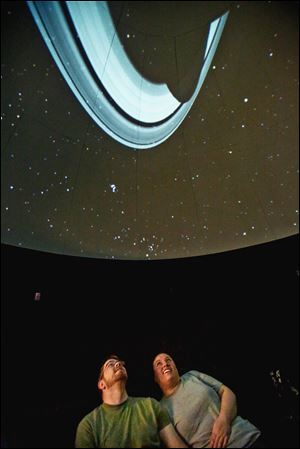 Chris McAnall and Sarah Sobel-Poage, both of Perrysburg, view a projection of the rings of Saturn on the dome of the Appold Planetarium at Lourdes University in Sylvania.
