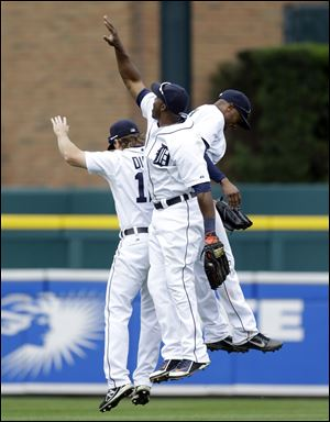 Detroit Tigers outfielders Andy Dirks, left, Torii Hunter, and Austin Jackson celebrate their 3-2 win over the Kansas City Royals todayin Detroit.