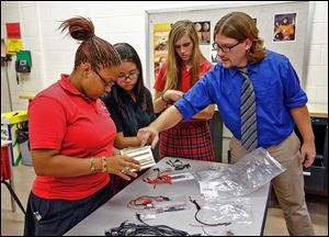 Eric Sieja speaks with, from left, juniors Sam Ferrell, Bonnie Jiang, and Sam Perry, right, while explaining the basics in electrical engineering at Cardinal Stritch High School in Oregon.
