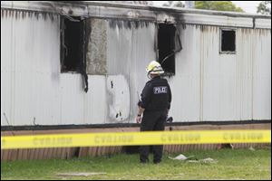 A state fire official inspects the mobile home in Tiffin where a fire killed a man and five children.