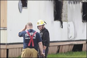 Wm. Timothy Spradlin, Chief of the Fire & Explosion Investigation Bureau with the Division of the State Fire Marshal, right, speaks with a member of Tiffin Fire & Rescue, left, during the investigation into the scene of a fire in Tiffin that killed 5 kids and one adult early this morning.