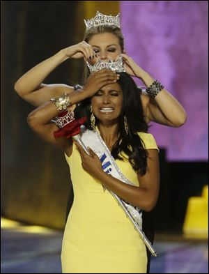 Miss New York Nina Davuluri, front, is crowned as Miss America 2014 by Miss America 2013 Mallory Haga on Sunday night in Atlantic City, N.J.