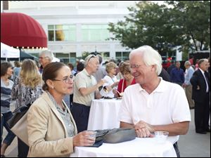Executive Director of the Toledo Opera Suzanne Rorick, left, and Chris Layne, right, chat during the plaza party at the Valentine Theatre.