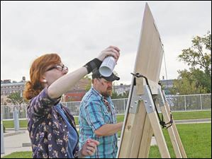 Artists Sarah Thomas, of Sylvania, left, and Matt Taylor, of Toledo, as they paint four panels that will be available for purchase at the Toledo Lucas County Public Library's Rockin' on the Rooftop event.