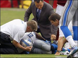 Detroit's Reggie Bush is attended to by training staff after injuring his knee Sunday against Arizona.