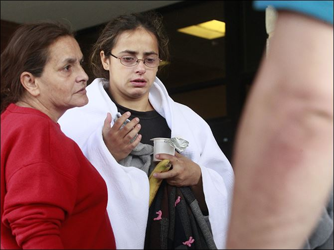 n3fire Anna Angel, whose five children and boyfriend were killed in a fire early Sunday morning, is comforted by her mother, Linda Ramirez, left, while leaving Mercy Hospital in Tiffin  on Sunday.