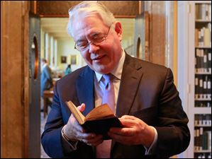 David Redden, vice chairman of Southeby's, holds the Bay Psalm Book.