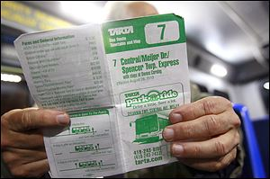 A bus rider holds the schedule for TARTA's Route 7, which runs to Spencer Township.