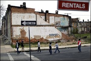 The national poverty rate held steady in 2012 at 15 percent, the Census Bureau reported last week. In this April 4 file photo, children walk past a partially collapsed row house in Baltimore.