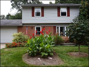The front yard features red canna flowers.
