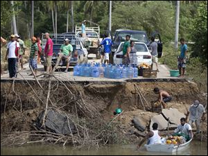 People stand on the edge of a collapsed bridge as they wait to ferry their goods via a boat across the Papagayos River, south of Acapulco.