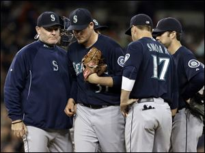 Seattle Mariners manager Eric Wedge, left, pulls starting pitcher Brandon Maurer in the sixth inning.