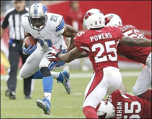 Detroit's Reggie Bush runs against Arizona. Bush hurt his knee in the game and might miss Sunday's game at Washington.