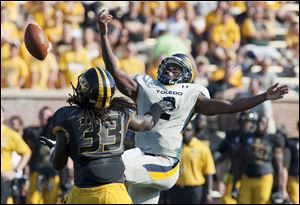 Missouri's Markus Golden, left, reaches to intercept the ball that slipped out of Toledo quarterback Terrance Owens' hand, right, before returning it for a touchdwon during the third quarter of an NCAA college football in Columbia, Mo.