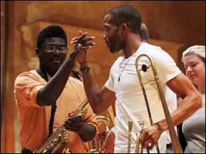 Toledo School for the Arts student Tyler Fowler gets a high-five from Trombone Shorty after performing together.