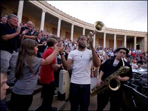 Trombone Shorty high-fives a fan as he leads his band and students from the Toledo School for the Arts around the Peristyle.