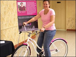 Shari McCague, a breast cancer survivor, sits astride the Komen Race for the Cure themed beach cruiser bicycle that she won in one of the raffle drawings at Confections for the Cure that was held on July 31 at the Toledo Elks Lodge Number 53.