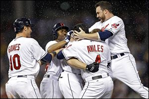 The Indians' Jason Kipnis, right, Mike Aviles, Michael Bourn, and Yan Gomes, left, mob Matt Carson after Carson's bases-loaded single in the 11th inning gave the Indians a 2-1 win over the Astros.