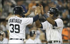 Detroit Tigers' Torii Hunter, right, celebrates with Ramon Santiago (39) after they scored on a Prince Fielder single in the fifth inning Friday in Detroit.