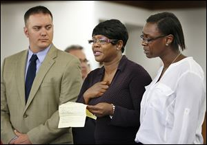Bernice Howard, mother of Brian Minley, accompanied by Arnisha Gainer, her daughter, right, makes a statement during the sentencing of Daquaine Booth in Lucas County Common Pleas Court on Friday in Toledo. Booth pleaded guilty to the murder of Mr. Minley and was immediately sentenced to life in prison by Judge Dean Mandros.  Assistant Lucas County Prosecutor Frank Sypryszak is at left.