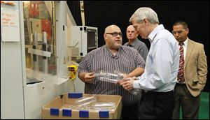 Tom Carros, left, discusses a machine that makes generic 2-liter pop bottles to Sen. Rob Portman during his tour Friday of the Plastic Technologies Inc. plant in Holland.