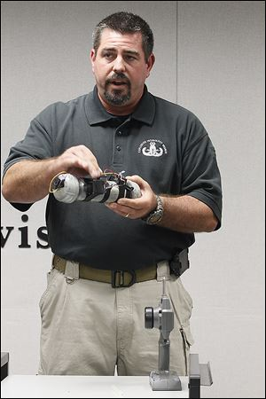 ATF Explosives Enforcement Officer Michael Eggleston demonstrates the workings of what authorities termed a 'basic representative' of the bomb used against the Chappells in Monroe two years ago. The bomber had to be in sight of the Chappell vehicle and no more than a half-mile away from it, Mr. Eggleston said.