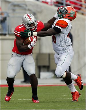 Ohio State TB Rod Smith (7) stiff arms  Florida A&M Colby Blanton (36) during the second quarter.