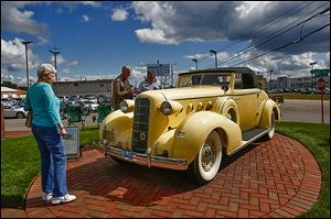 Noreen Greathouse of South Toledo takes a look at a 1935 LaSalle owned by Richard Zapala of Haslett, Mich.