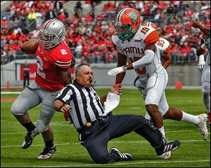 Ohio State's Jordan Hall knocks down an official on his way to to the end zone as Florida A&M's Jonathan Pillow gives chase. The Buckeyes built a 55-0 halftime lead.