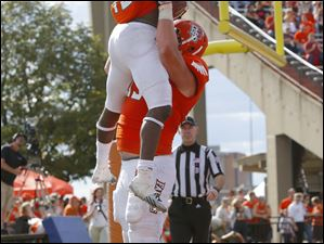 Bowling Green State University player Travis Greene (13) is hoisted in the air by teammate Alex Huettel (55) after scoring a touchdown.