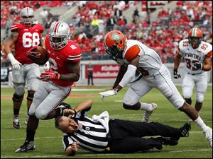Ohio State TB Jordan Hall takes out an official on his way to scoring a touchdown against  Florida A&M SS Jonathan Pillow (19) during the second quarter.