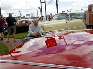 Cadillac enthusiasts, including Rob Vick, of South Toledo, center, snapped pictures of a 1959 convertible owned by Duke Gercke of Berlin Heights.