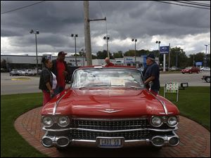 Cadillac enthusiasts take a look at a 1959 convertible.