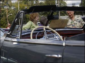 Vicki Haas, 70, left, and Alan Haas, 73, of Sylvania, right, chat while taking a look at several classic cars.