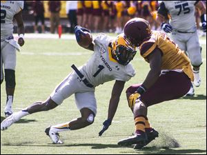 Toledo Rockets wide receiver Bernard Reedy tries eluding a Central Michigan defender after a catch.