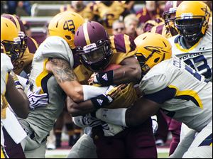 Toldeo Rockets defenders tackle Central Michigan's Anthony Garland.